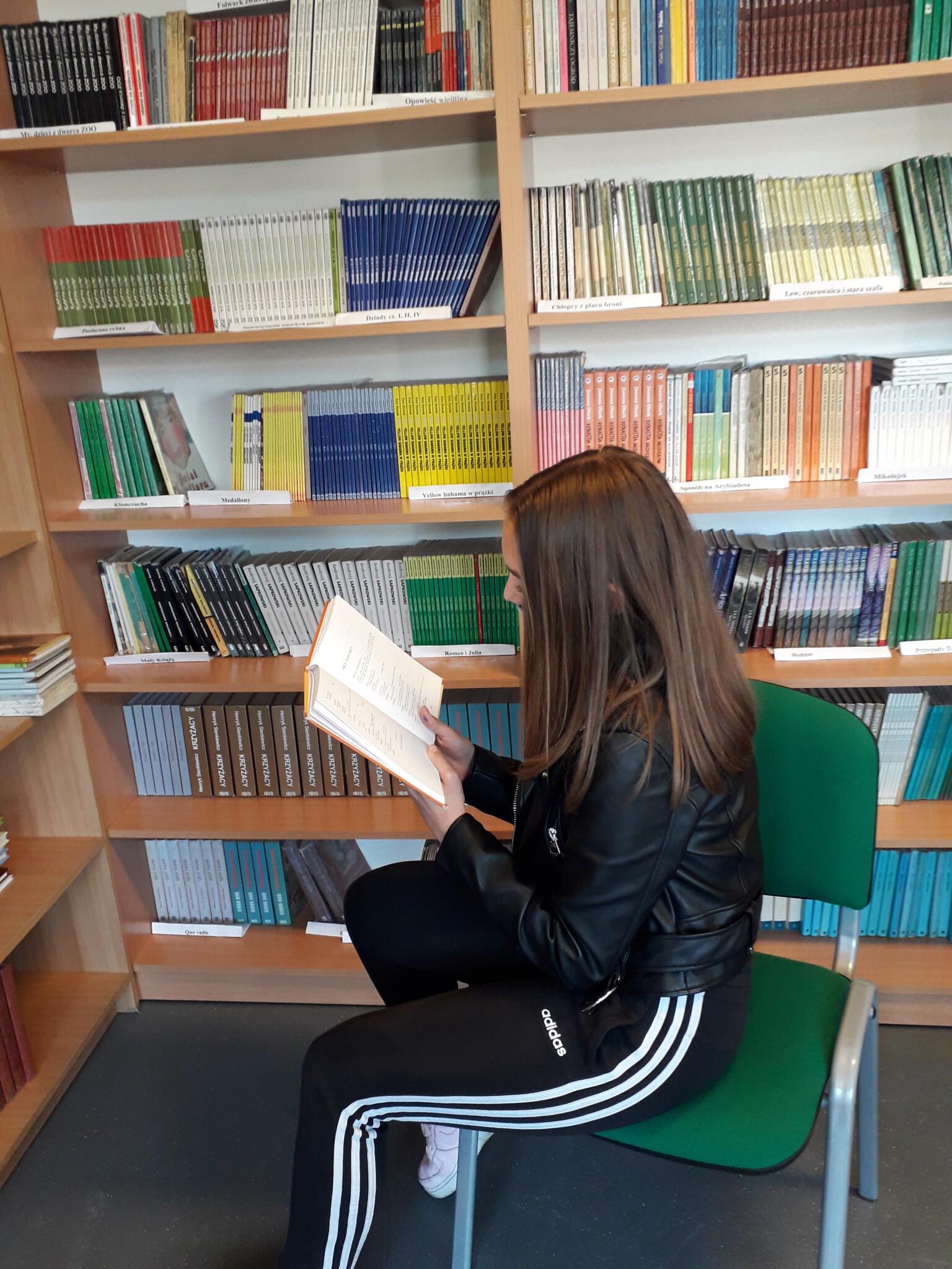 zdjęcie przedstawiające dziewczynę czytającą książkę w bibliotece