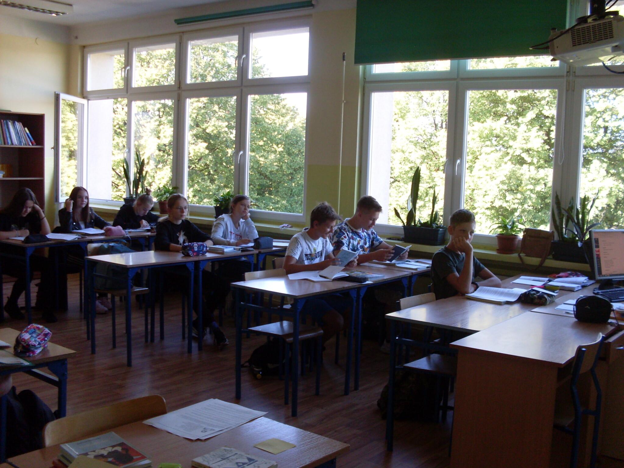 Zdjęcie klasy czytającej Balladynę w sali lekcyjnej